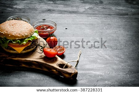 Burger with the ingredients and sauce on the Board. On a black chalkboard. - stock photo