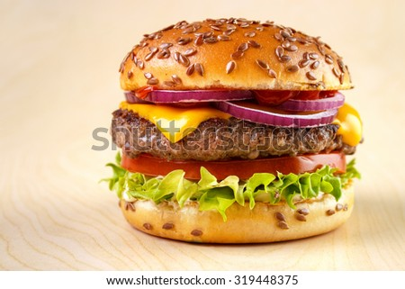 Burger with tomato , lettuce , mayonnaise , cheese , onion , ketchup and flax seeds on bun , yellow wooden background - stock photo