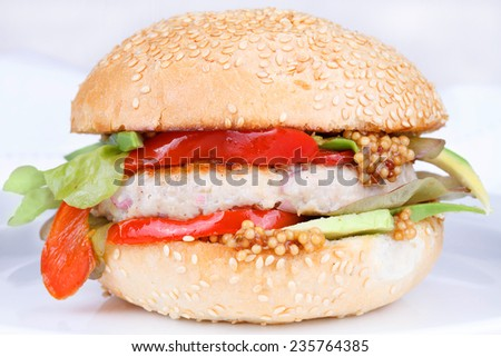 Burger with turkey, lettuce, onions, red paprika pepper on a sesame seed bun.