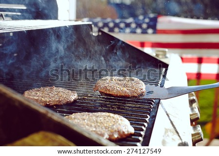 Burgers and hotdogs cooking over flames on grill - stock photo