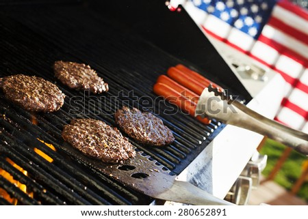 Burgers and hotdogs cooking over flames on grill