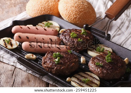 burgers and sausages with vegetables on a grill pan closeup. horizontal