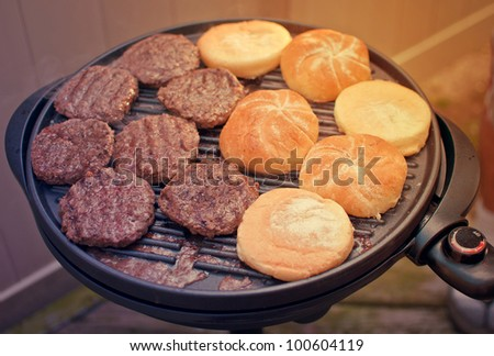 Burgers on grill - stock photo
