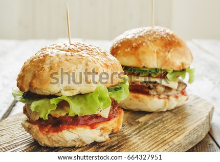 Burgers with beef, onion, tomato and lettuce on wooden cutting board. Close up