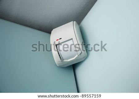 burglar alarm movement sensor mounted on a wall - stock photo