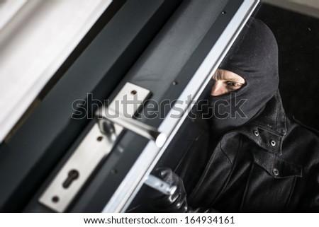 Burglar breaking in - stock photo