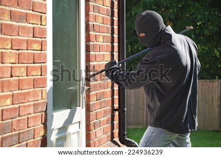 Burglar breaking into a house via a door with a crowbar - stock photo