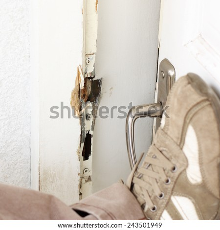 Burglar breaking into a house with foot - stock photo