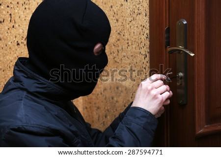 Burglar breaking into house - stock photo