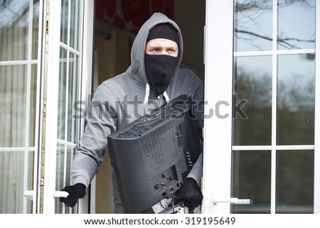 Burglar Breaking Into House And Stealing Television - stock photo
