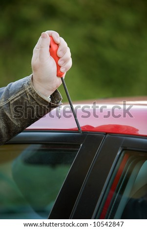 Burglar breaks into a car - stock photo