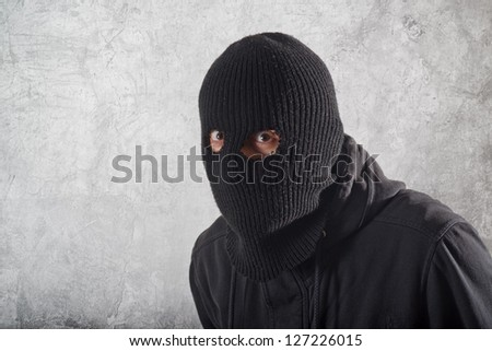 Burglar concept, thief with balaclava caught in front of the grunge concrete wall. - stock photo
