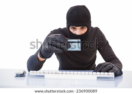 Burglar doing online shopping with laptop and credit card on white background - stock photo