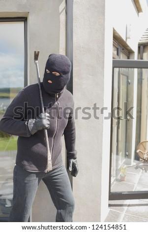 Burglar hiding behind wall with crow bar in back garden - stock photo