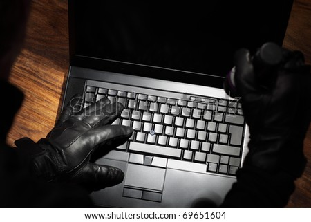 Burglar holding a torch stealing data from a laptop concept for computer security, corporate or identity theft - stock photo