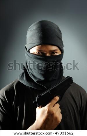 Burglar holding pistol - stock photo