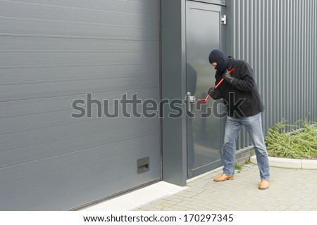burglar in disguise to open an industrial door with brute force - stock photo