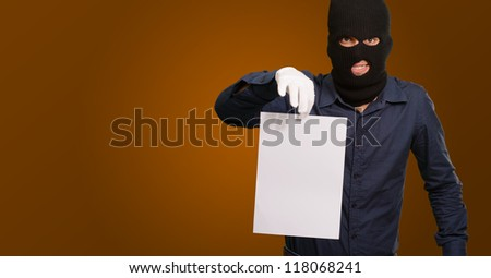 Burglar In Face Mask On Brown Background