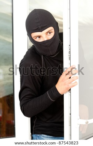 burglar  in mask and balaclava breaking into a house through window - stock photo