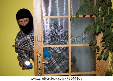 burglar in mask breaking into a house through door - stock photo
