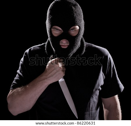 Burglar in mask holding knife on black background - stock photo