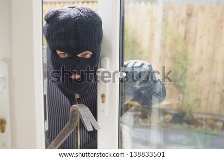 Burglar looking if someone is into the room - stock photo