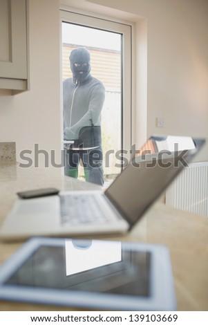 Burglar opening kitchen door and looking at laptop on counter of kitchen - stock photo