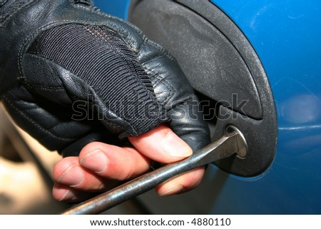 Burglar trying to open the car on harder way - stock photo
