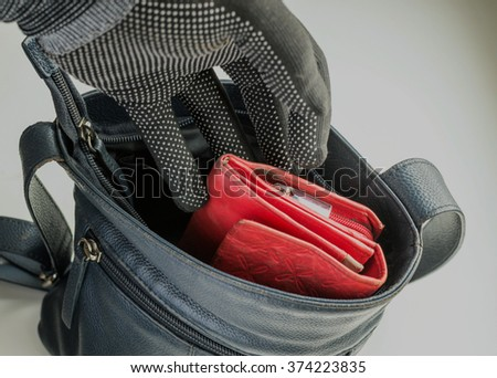 Burglar type thief wearing a black glove attempts to commit a crime by stealing a woman's red leather purse from her unattended blue handbag - stock photo
