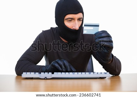 Burglar typing on keyboard and holding credit card on white background - stock photo