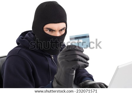 Burglar using credit card and laptop on white background - stock photo