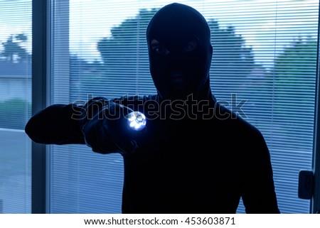 Burglar wearing a balaclava looking through the house window - stock photo