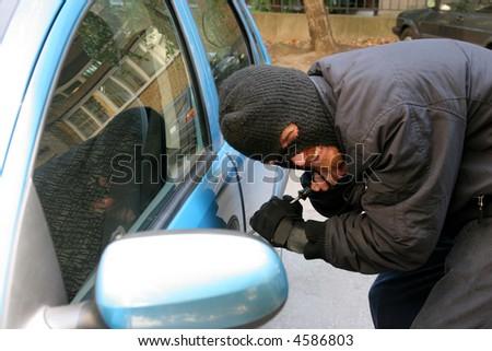 burglar wearing a mask (balaclava), car burglary - stock photo