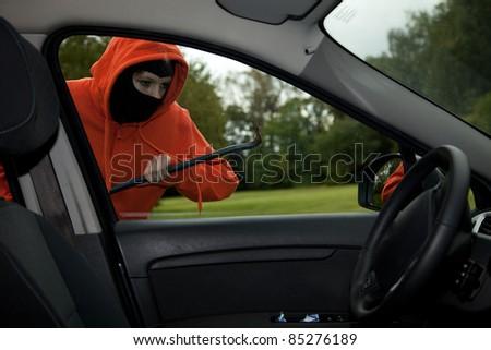 Burglar wearing a mask (balaclava), car burglary, series - stock photo