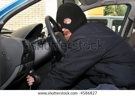 burglar wearing a mask (balaclava), details car burglary inside - stock photo