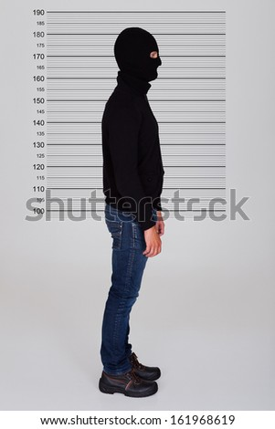 Burglar Wearing Balaclava Standing Against Police Lineup - stock photo