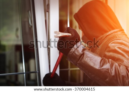 Burglar wearing black clothes and leather coat breaking in a house - stock photo