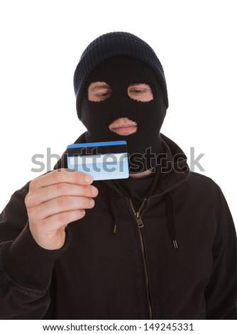 Burglar Wearing Mask Holding Credit Card Over White Background - stock photo