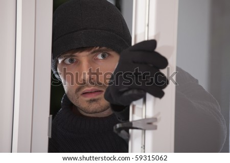 burglar with crowbar breaking into a house through glass door - stock photo