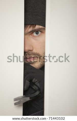 Burglar with crowbar breaks into a house - stock photo