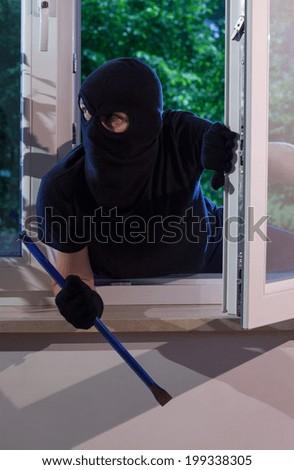 Burglar with crowbar in his hand looks around the apartment - stock photo