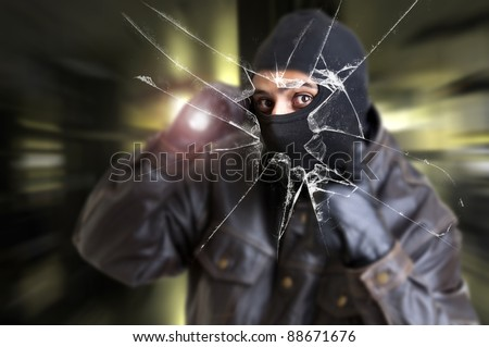 Burglar with flashlight over a broken glass - stock photo