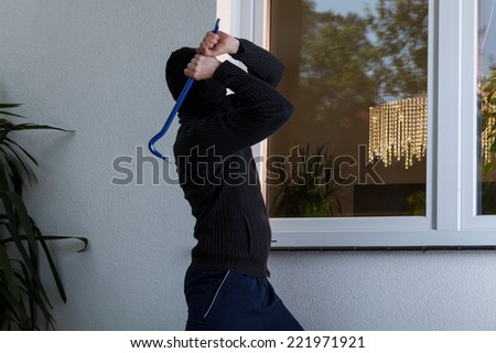 Burglar with obscured face trying to break the window - stock photo