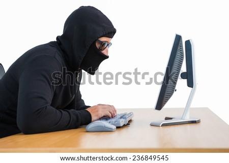 Burglar with sunglasses typing on keyboard on white background - stock photo