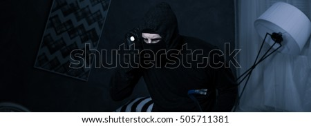 Burglar with the black blouse searching something in room at night