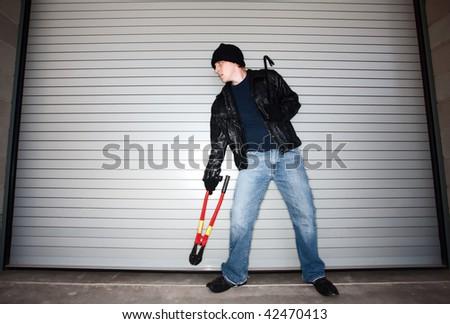 Burglar with tools in front of industrial door - stock photo