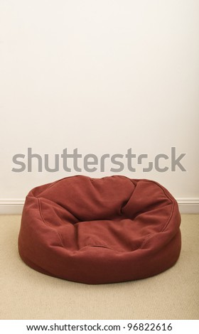 Burgundy bean bag on the floor near the wall. - stock photo