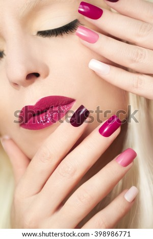 Burgundy colored manicure closeup on the nails and the makeup on the girl. - stock photo