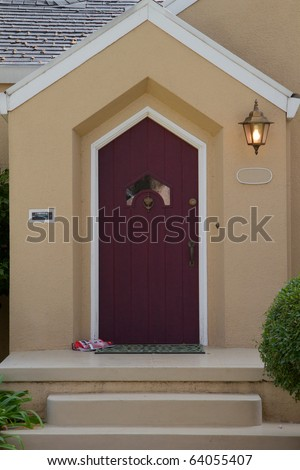 Burgundy door with unusual window on a white trimmed beige house with a lamp - stock photo