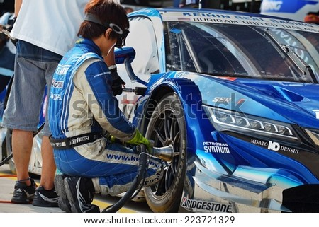 Buriram THAILAND - October 5:Car mechanic in uniform. Auto repair in the Super GT race car 2014 at Chang International Circuit in Buriram United, on October 4-5, 2014 at the Buriram, Thailand. - stock photo